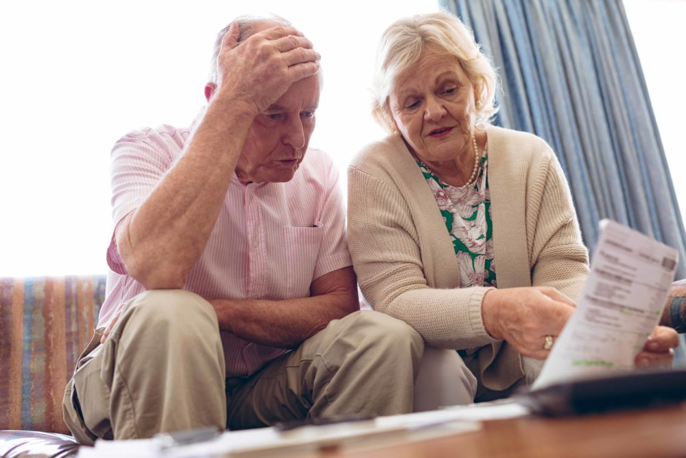 Front view of worried senior Caucasian couple discussing over medical bill while sitting on sofa at retirement home. Senior male has hand on his head.